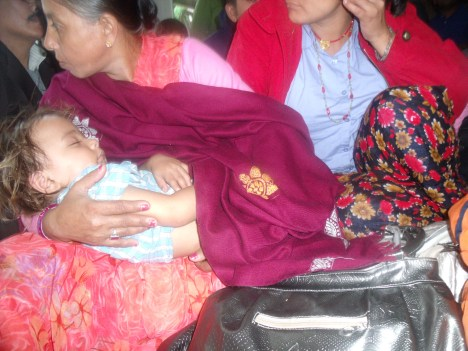 A one year child sleeping in the lap of a relative Bhutanese women in the get together program